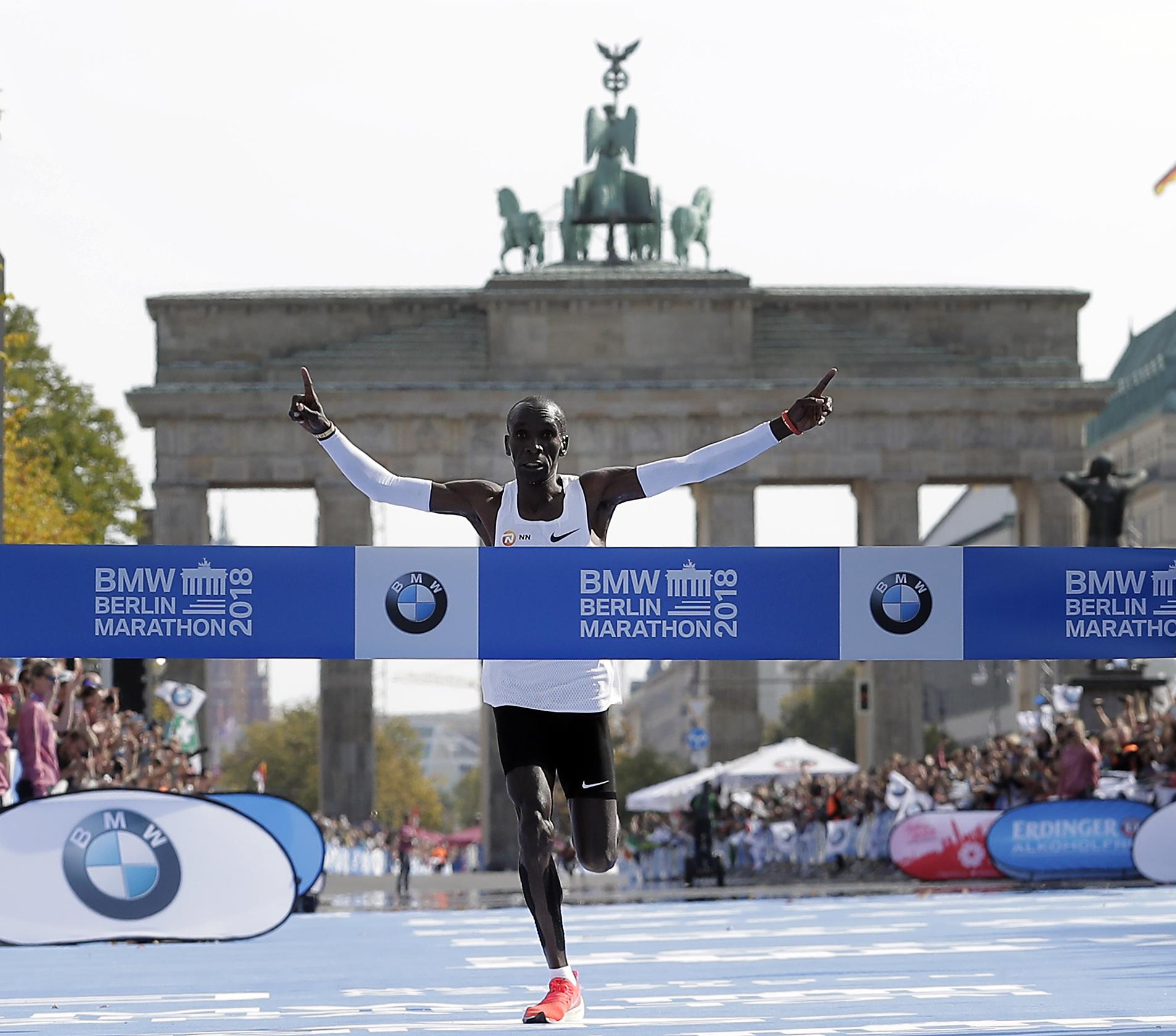 Kipchoge spreads his arms in celebration at the finish line outside the Brandenburg Gate in Berlin