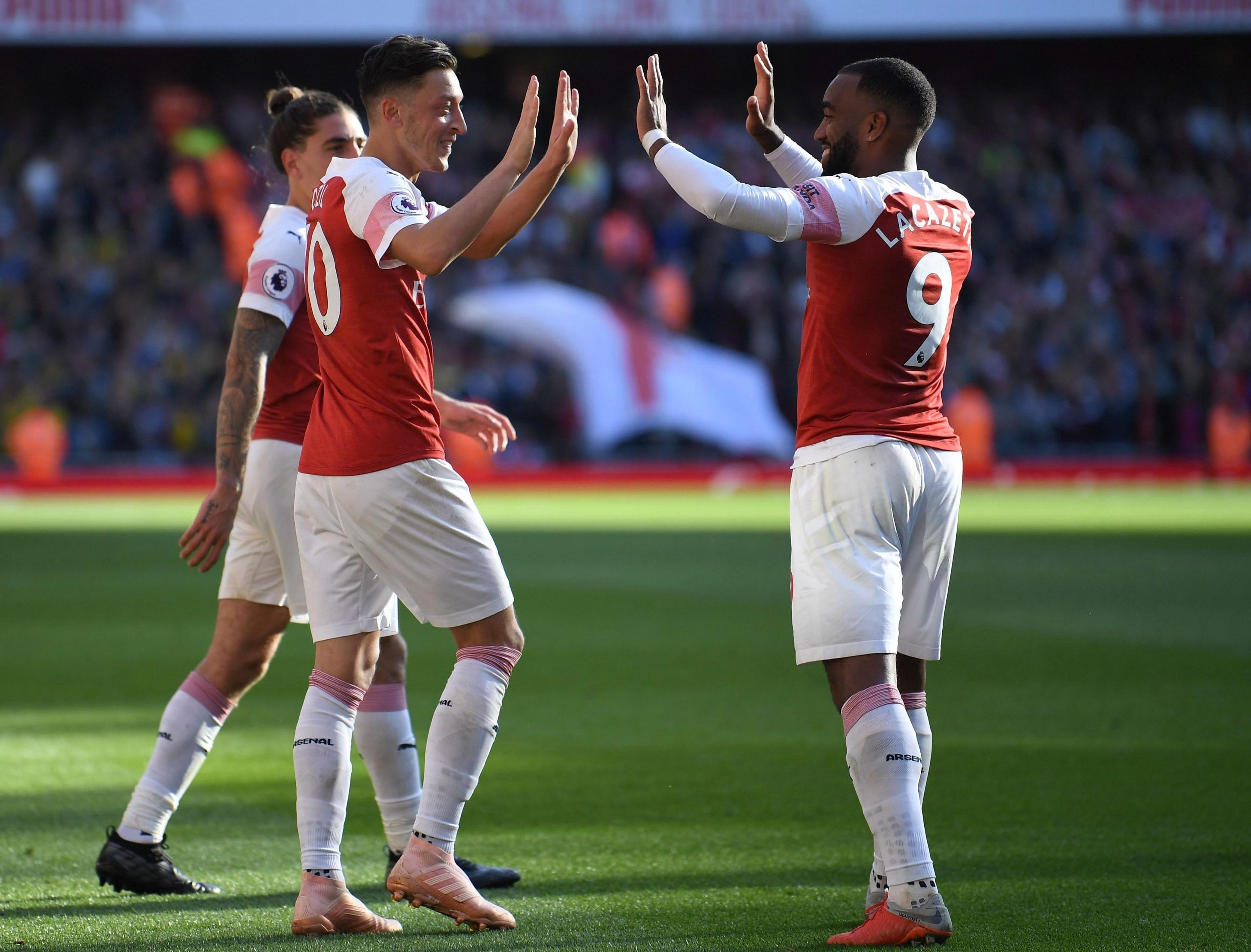 Ozil, left, celebrates with Alexandre Lacazette after Arsenal's seventh straight win