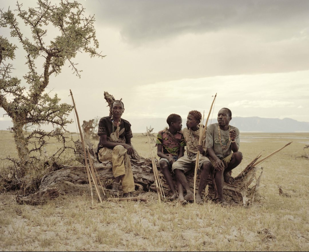 Giaga, 50, Manu, 14, Osama, 15, and Madenye , 46 , sit and rest on a dead tree