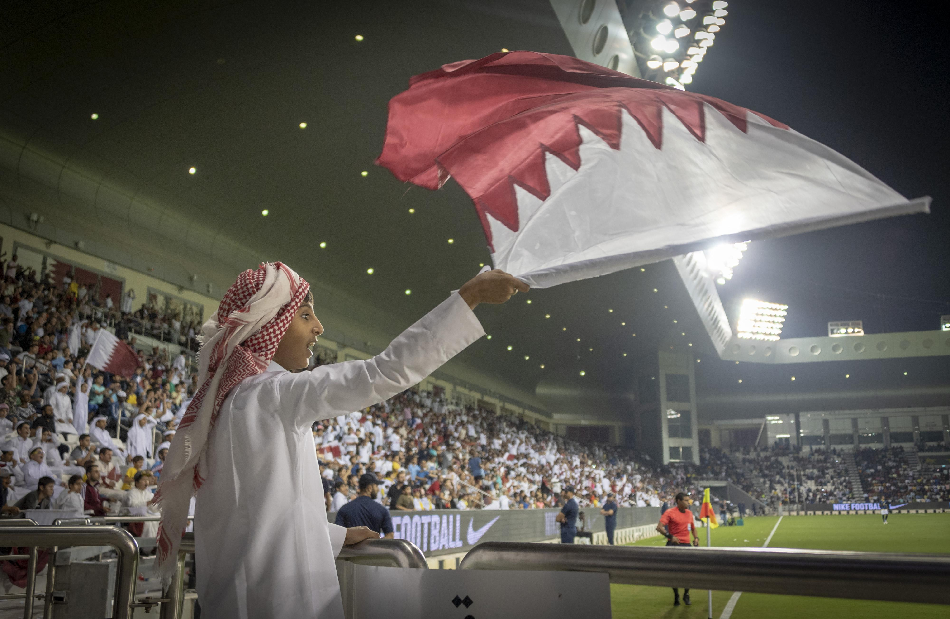 A young Qatar fan waves the national flag in a 4-3 friendly win over Ecuador