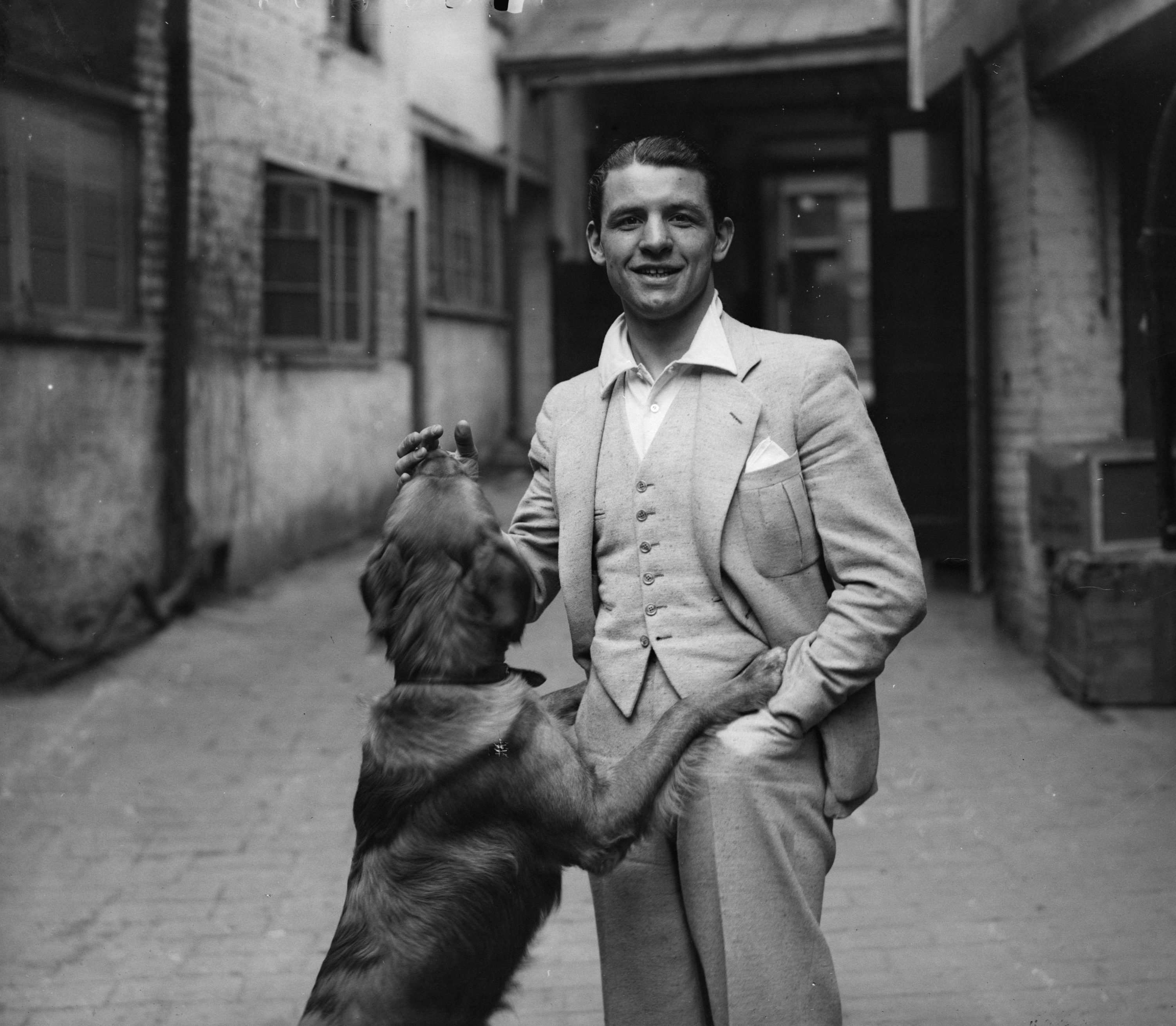 Jack 'Kid' Berg is shown playing with a dog at Windsor before fighting Italian lightweight champion Cleto Locatelli