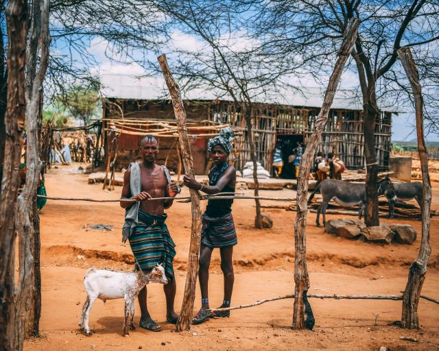 Two Hamar people with a small goat in the middle of their community