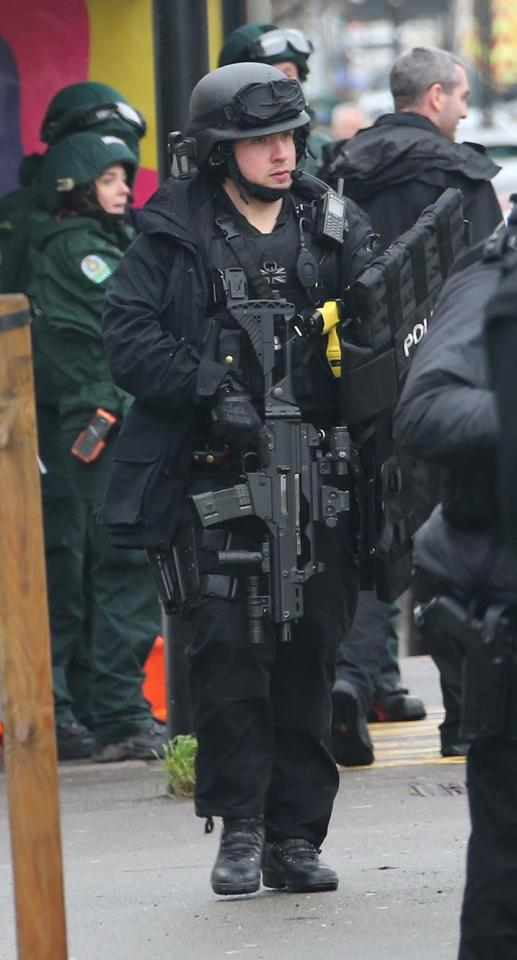 A heavily armed police stands at the scene