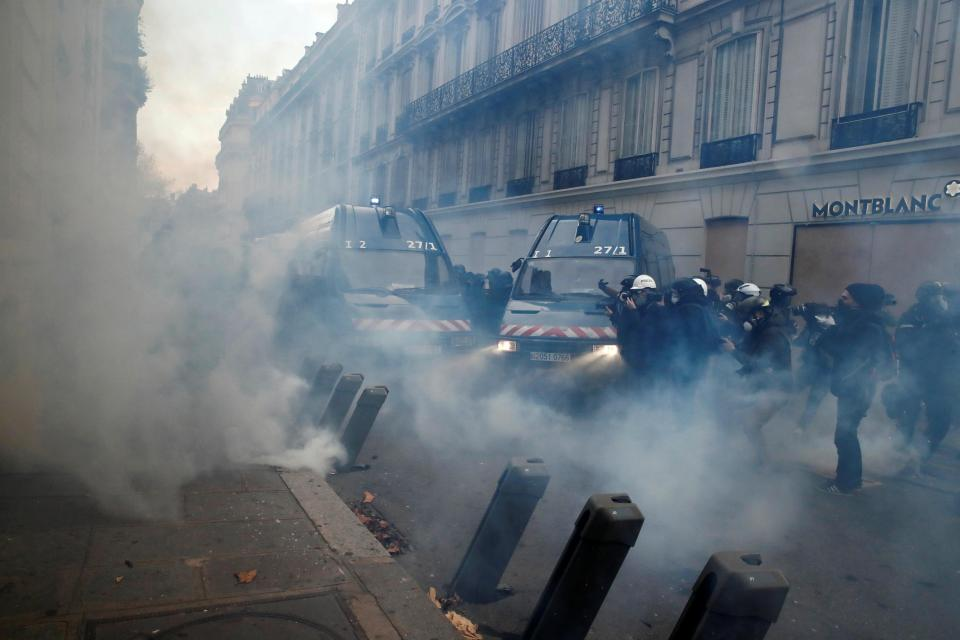 Police threw tear gas at protesters in a side street of the Champs Elysées