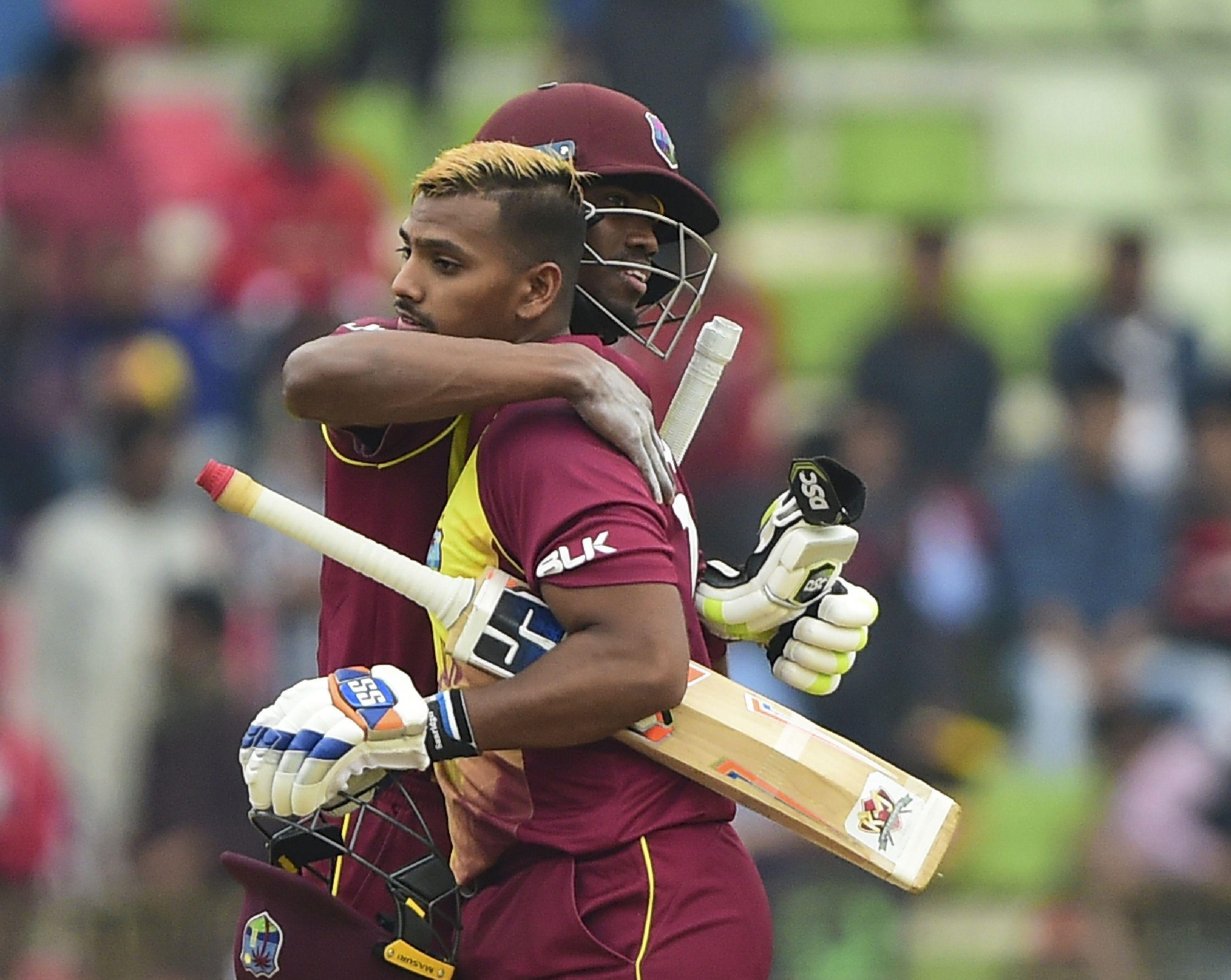 West Indies cricketer Keemo Paul (left) embrace with his teammate Nicholas Pooran (right) after winning the first Twenty20 (T20) cricket match between Bangladesh and West Indies