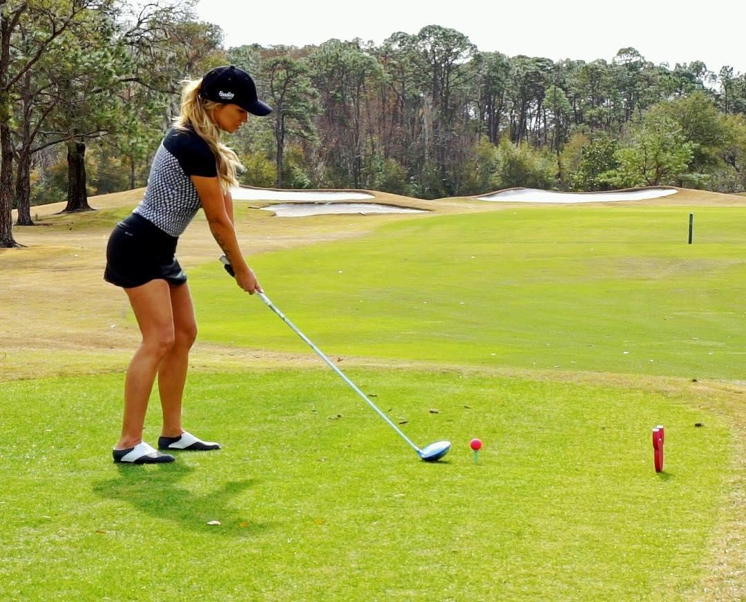 When she's not posing for the camera, she is brushing up her golf skills