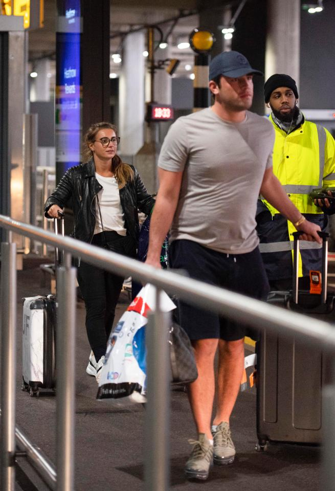 The couple kept their distance as they walked through through arrivals