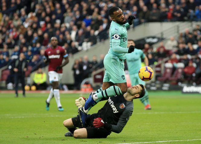 Lukasz Fabianski feels the full force of Alexandre Lacazette as he blocks the Arsenal striker