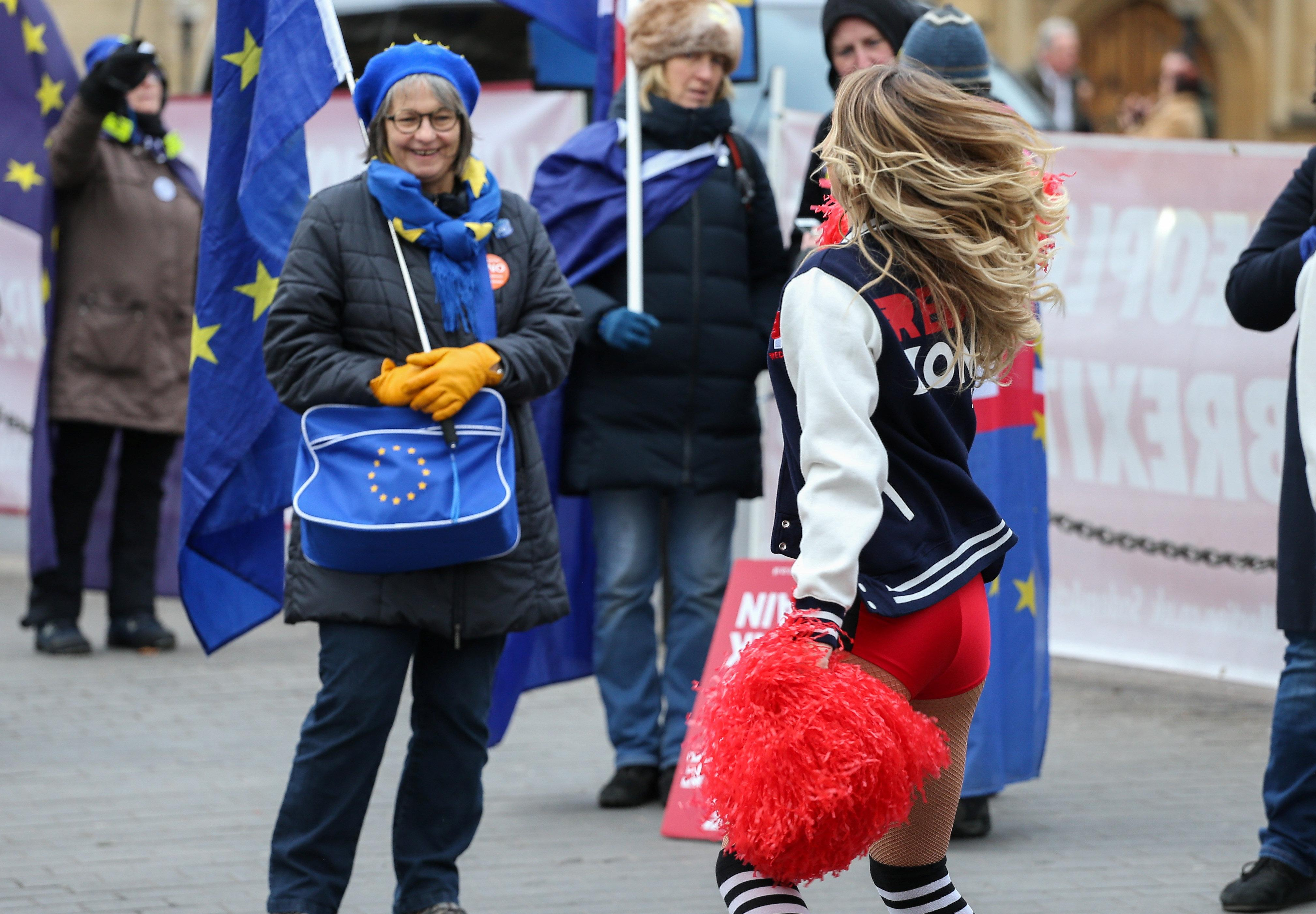 An anti-Brexit campaigner stops to admire the cheerleaders' performance