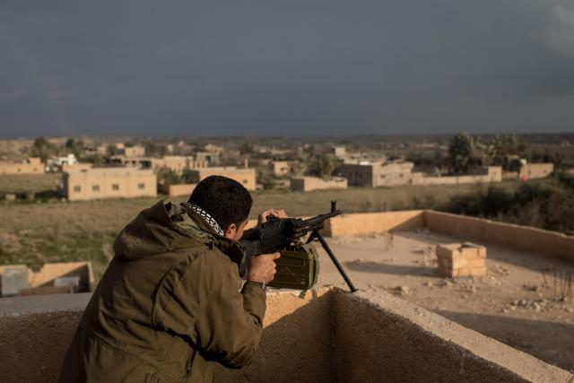 An SDF soldier takes up position on a roof top ready to mow down ISIS troops should they flee their under fire positions