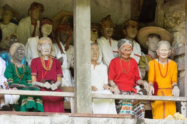 Wooden effigies represent the deceased who are in coffins in the cliffs