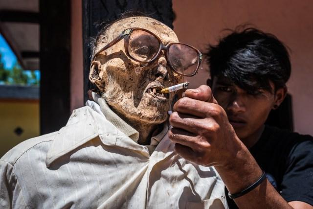 A boy gives an ancestor a cigarette