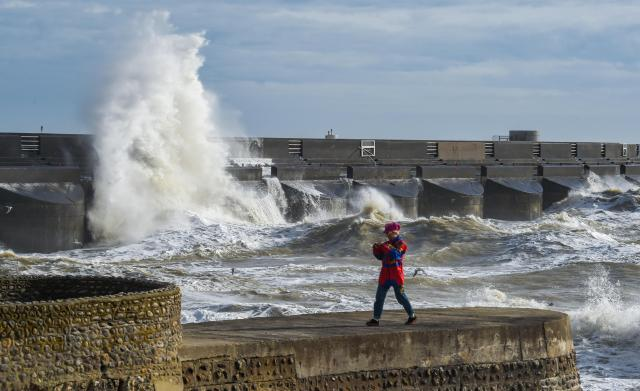 Onlookers watch huge waves crashing into the Brighton Marin
