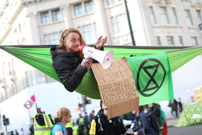 A climate change activist in a hammock occupying Oxford Circus in the busy shopping district