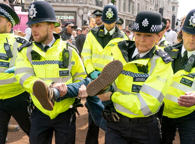 Climate change protesters have been asked to swarm Heathrow Airport tomorrow as Easter holidays begin - pictured is a protester being removed from Oxford Circus