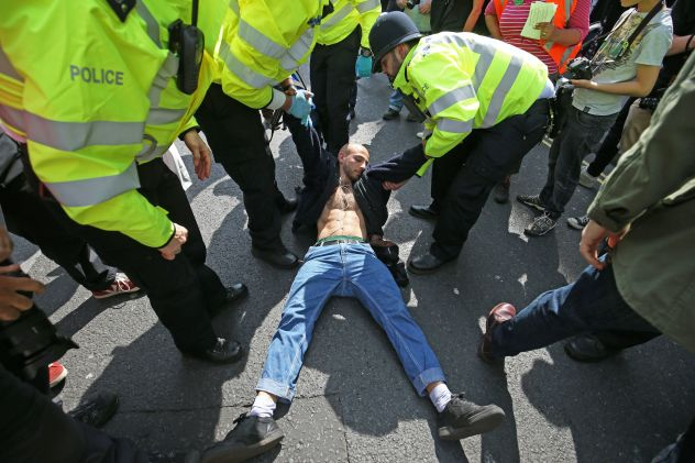 One man lays on the ground to stop police from arresting him