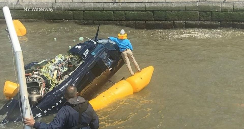 Helicopter pilot Eric Morales clings onto the aircraft as he waits to be rescued from the Hudson River in New York City