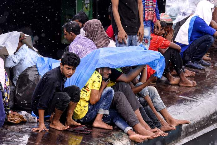 Bangladeshis cover themselves from the rain as they wait for the next train to arrive