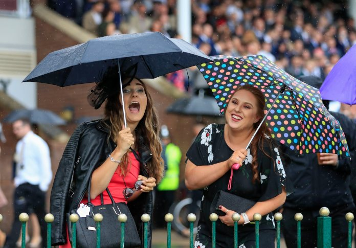 Two revellers braved the rain at the Haydock Park Racecourse in Merseyside yesterday