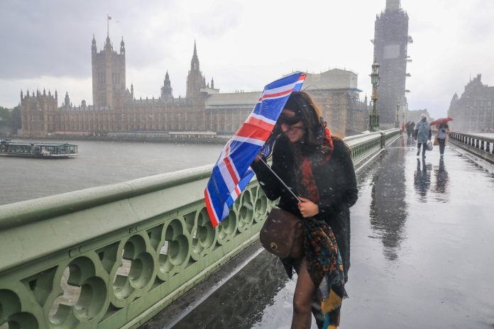 A woman was seen battling torrential downpours on Westminster Bridge last week