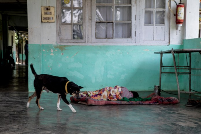 A child sleeps on a thin blanket on the ground in Assam