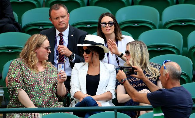 A spectator takes a photo of the Duchess of Sussex during the game