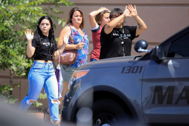 Shoppers exit with their hands up after a mass shooting in Texas