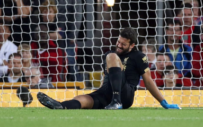 Liverpool goalkeeper Alisson grimaces with pain after the freak accident