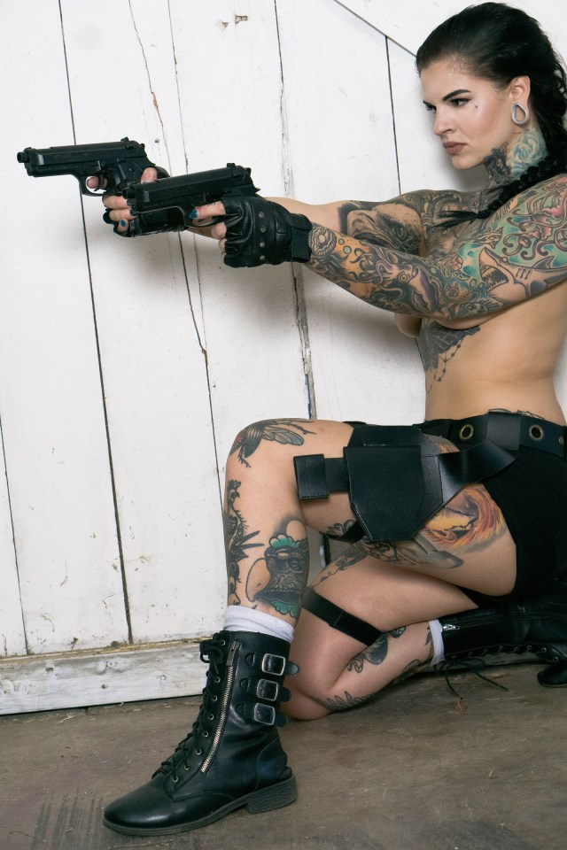 Heidi poses topless with two handguns in this snap