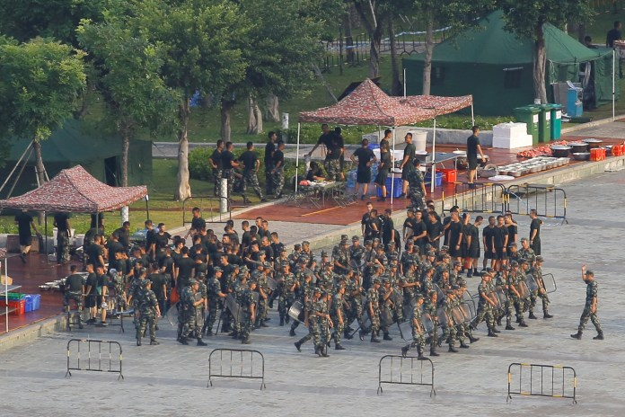 Chinese soldiers walk in formation on the grounds of the Shenzhen Bay Sports Center