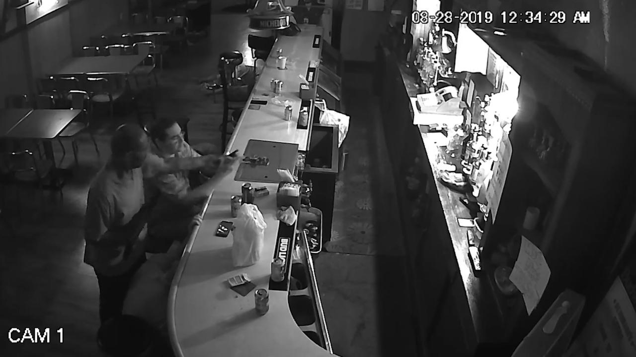 Tony relaxes at the bar despite a gunman pointing a pistol at him