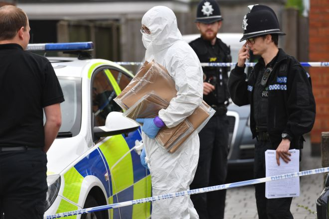Police and forensic officers outside the house in Burton-on-Trent, Staffordshire, today
