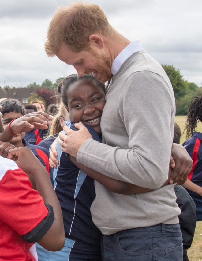 A student grins as she hugs Prince Harry during his school visit today