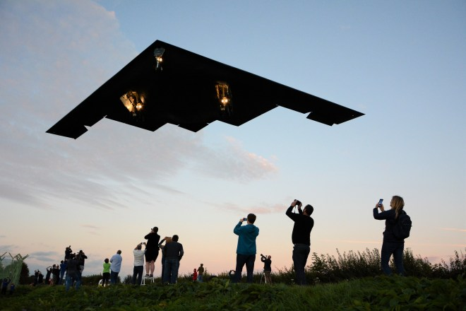 One of three bat-winged B-2 stealth bombers swoops over plane spotters as it returns from a war game mission