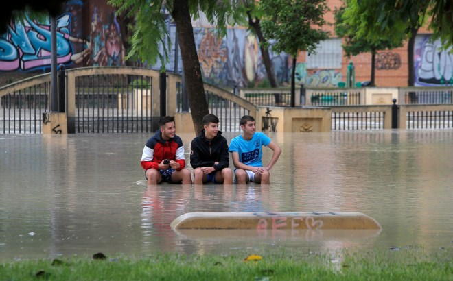 Boys sit on a bench in a park near the overflowing Segura river near Murcia