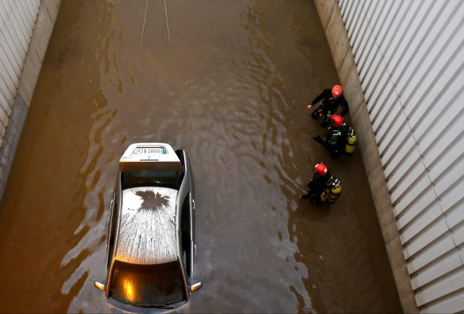 Emergency crews recover the car of a man who died after he became trapped in a flooded tunnel in Almeria