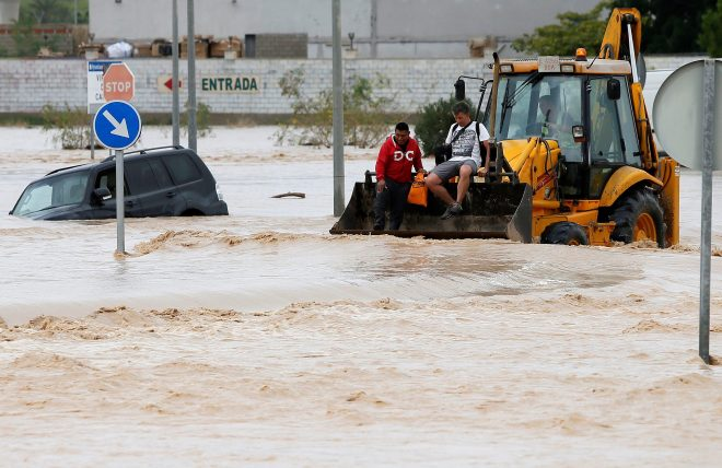 Two rescued men remain on top of a bulldozer on a flooded street in Orihuela, Alicante