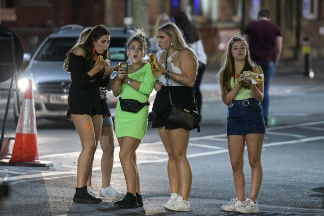 A group of women chow down on a takeaway in Birmingham as thousands came out for a bar crawl by Aston University to kick off Freshers Week