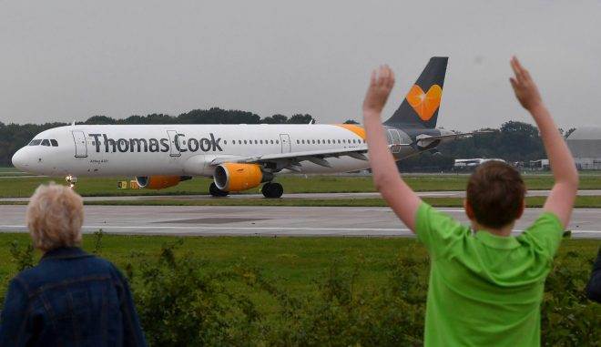 Pilots family members wave as a Thomas Cook flight departs Manchester Airport