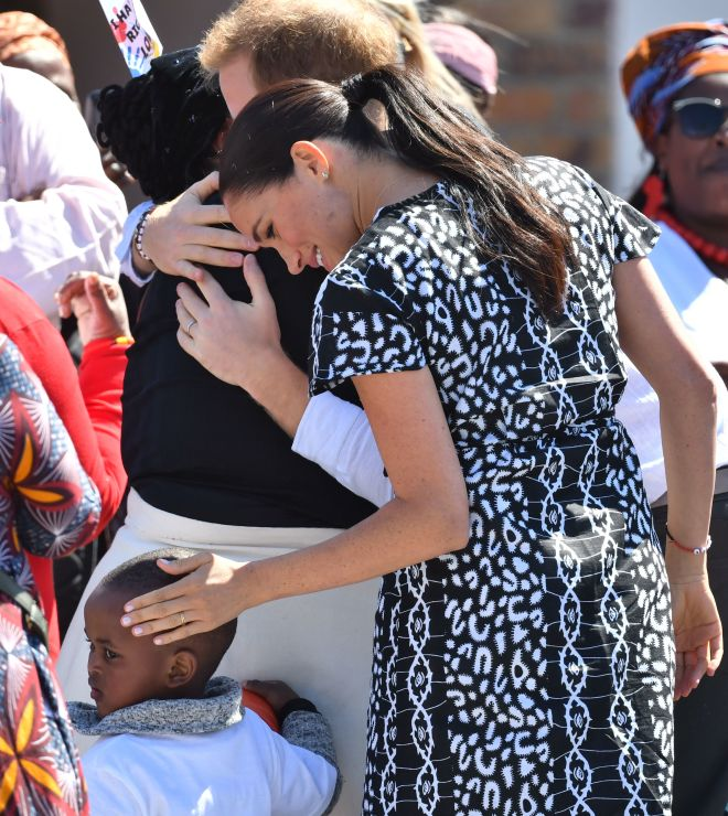 Meghan sweetly caresses child's head