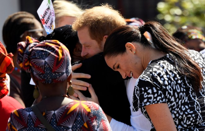 Harry gives a warm embrace to a resident of the township
