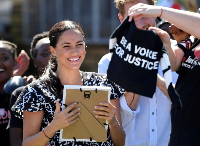 Meghan cracks a smile as a T-shirt is gifted to Archie with a slogan 'be a voice for justice'