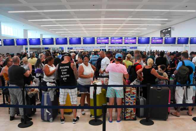 Passengers queue at the closed Thomas Cook check-in desk at the International Airport in Cancun, Mexico,