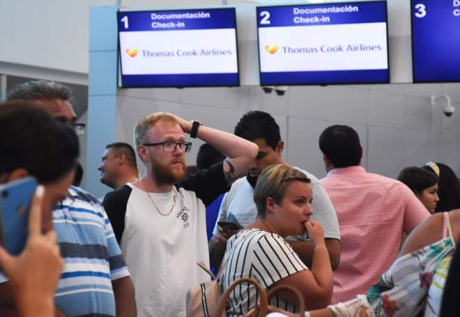 One passenger looks exasperated as he waits for information at the Thomas Cook check-in desk in Cancun