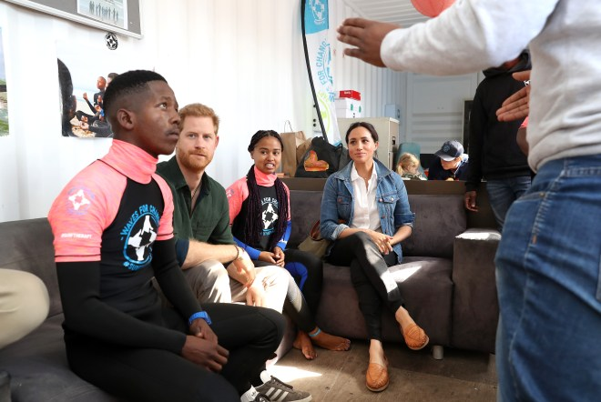 Prince Harry and Meghan Markle sit with some of the surfers during the morning tour of the charity's HQ