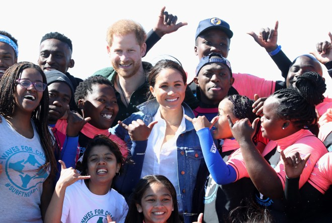 Meghan and Harry grin alongside young members of the charity