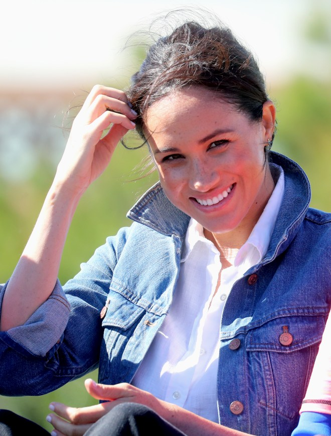 Meghan tucks a strand of hair behind her ear after the windy day