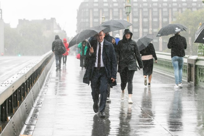 Pedestrians are caught in heavy downpours on Westminster Bridge in London