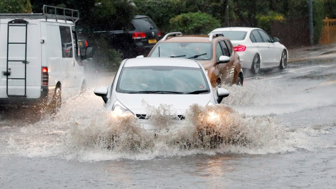 A car is driven into a flooded section of road after heavy rain caused localised flooding in Milton Keynes