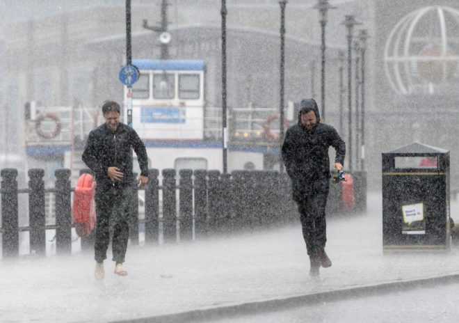 Office workers dash for cover during torrential rain in Newcastle today